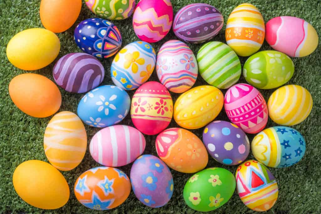 Happy Easter with colorful eggs at paintbrush for do it yourself on the grass with close up from top view.