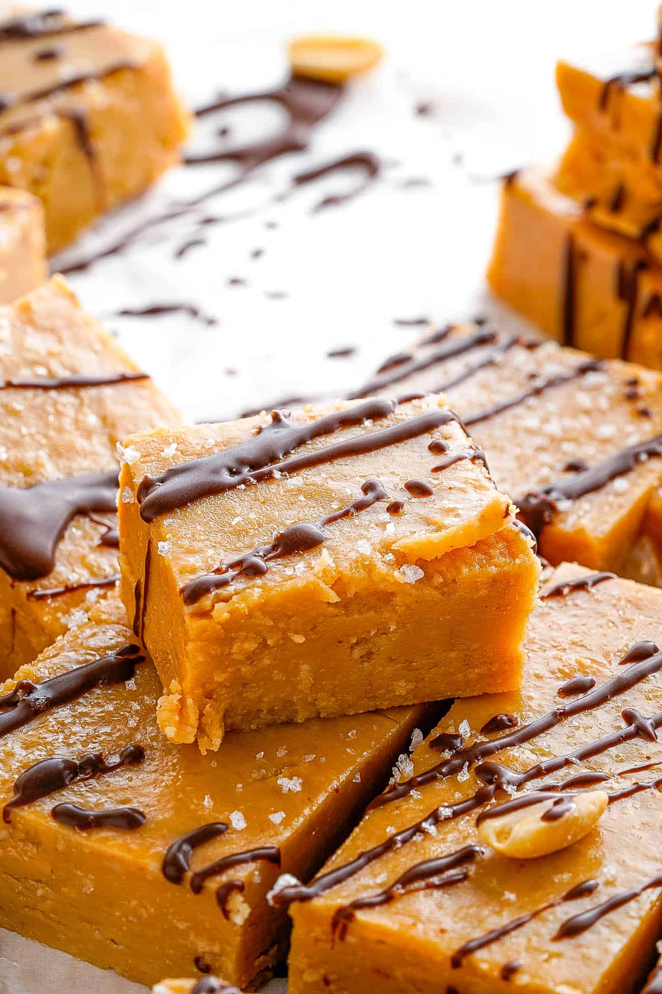 easy microwave chocolate peanut butter fudge cut into squares on parchment paper