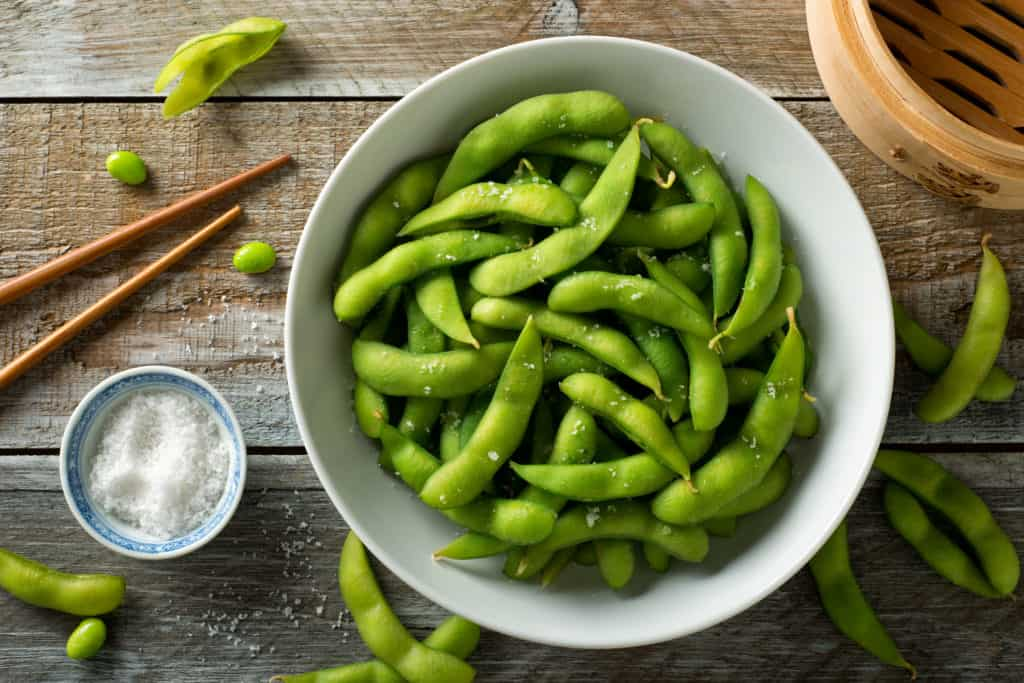 foods that start with E - Fresh steamed edamame sprinkled with sea salt on a rustic tabletop.