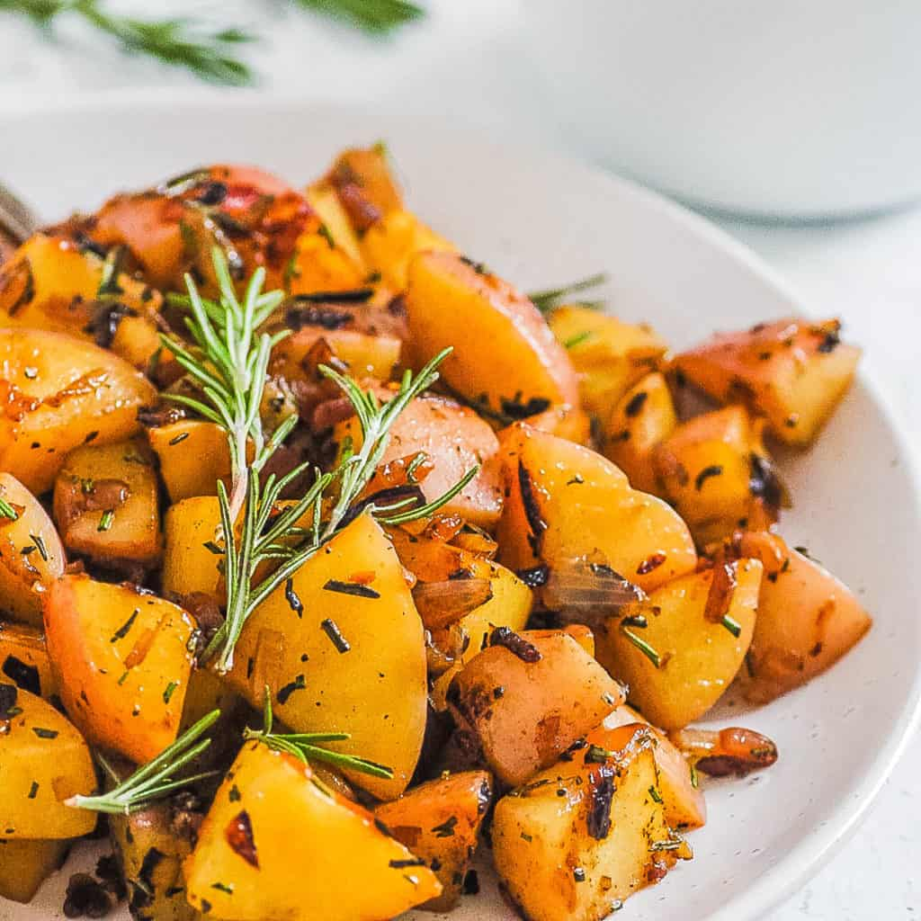 fried potatoes and onions served on a white plate with rosemary on top