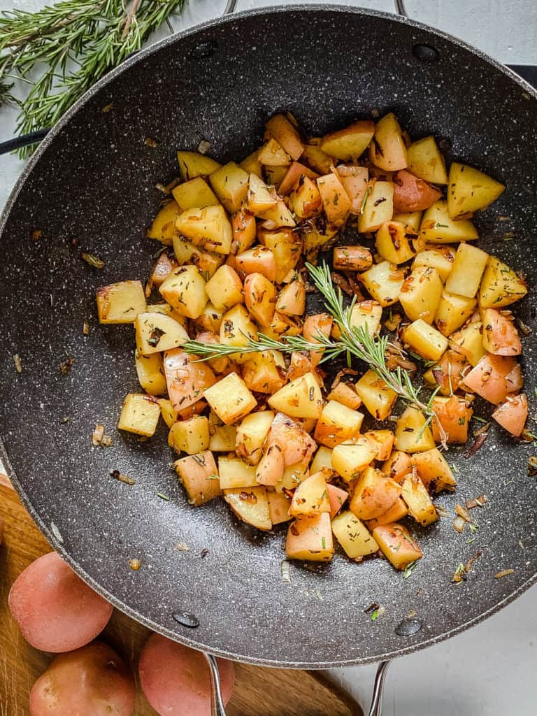 potatoes onions and herbs in a pan