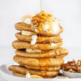 Healthy Pancakes stacked on a white plate with oatmeal and bananas and nuts and syrup