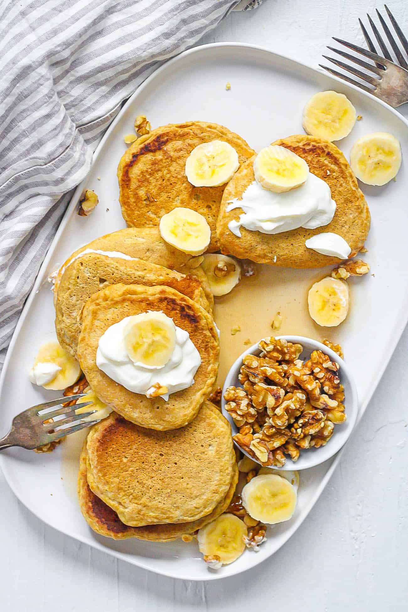 Healthy Pancakes spread out on a white plate with oatmeal and bananas and nuts and syrup