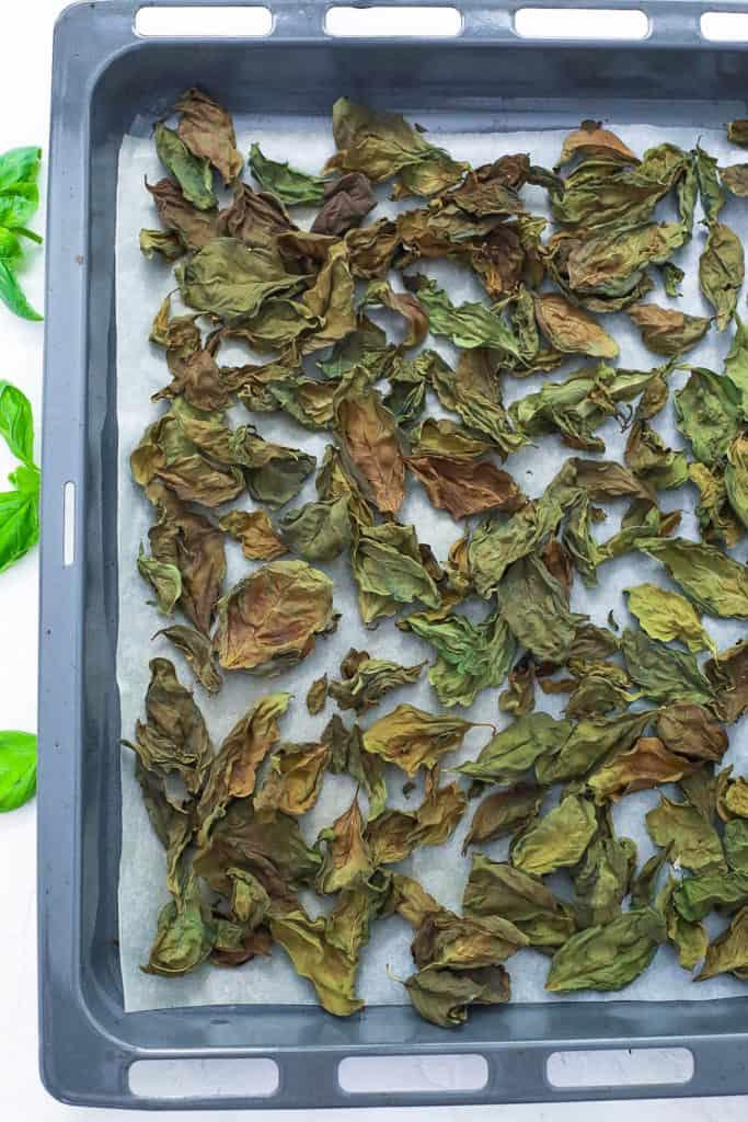 dry basil leaves on a baking sheet