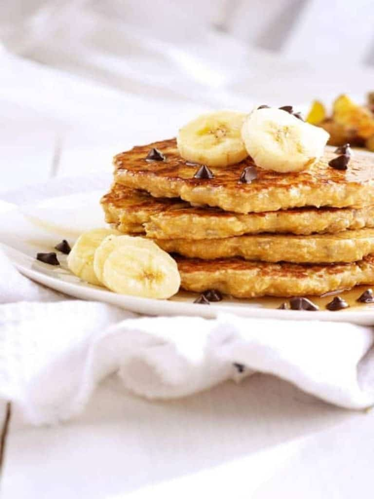 oat flour pancakes on white plate with banana slices