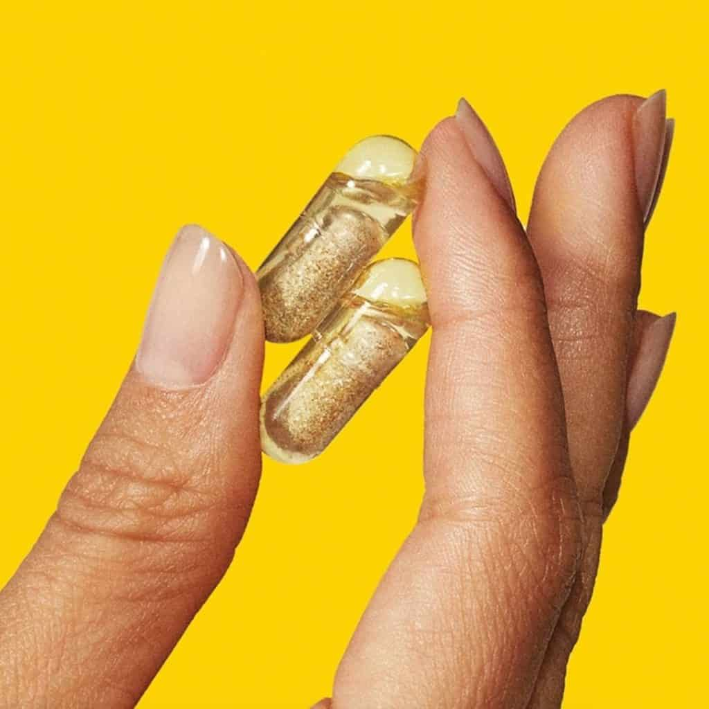 Two fingers holding two vitamin capsules on yellow background
