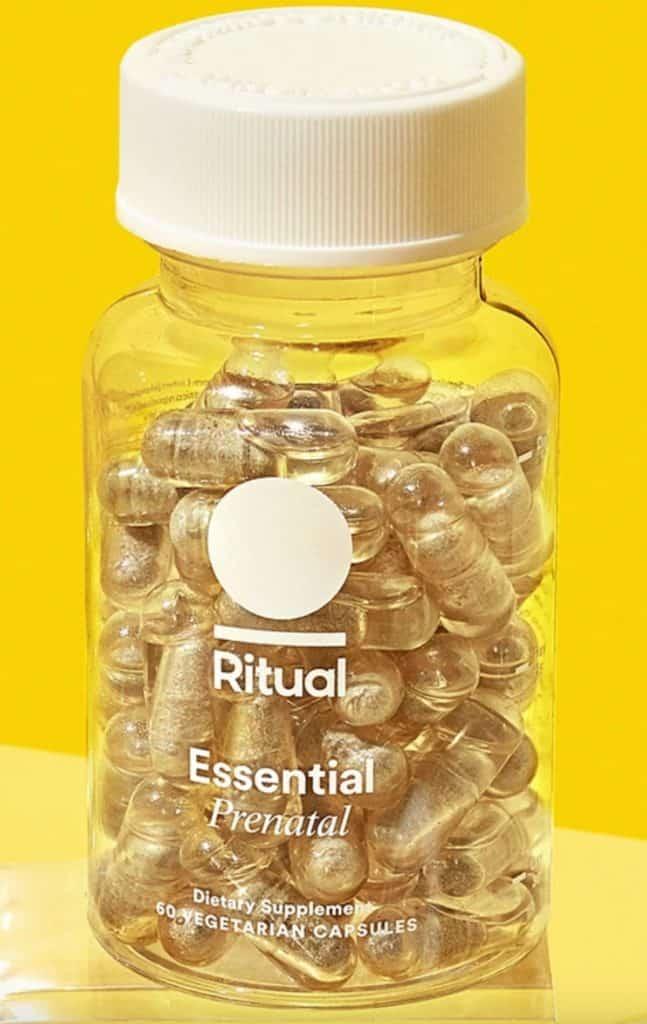 Bottle of Ritual Essential Prenatal Vitamins on yellow backdrop.