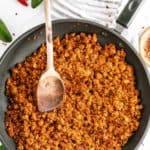 Vegan Chorizo in pan with wooden spoon.