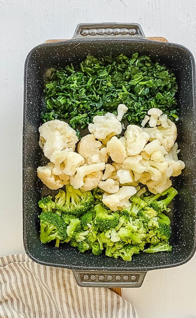 broccoli spinach and cauliflower on a cutting board
