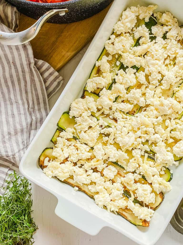 ricotta cheese on top of zucchini in baking dish