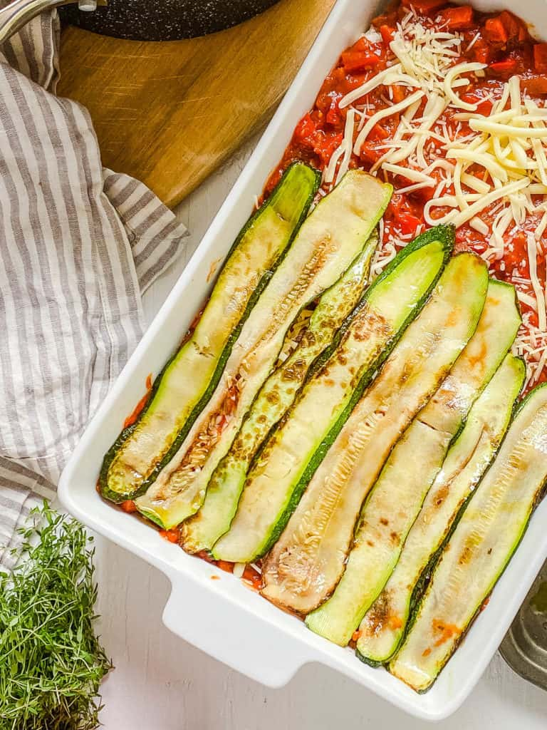 zucchini layers in casserole dish with cheese and sauce