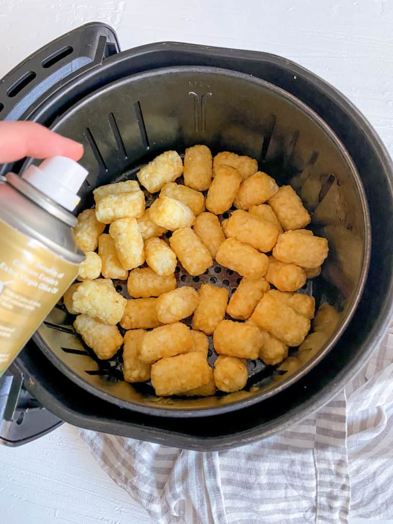tater tots in air fryer basket sprayed with olive oil
