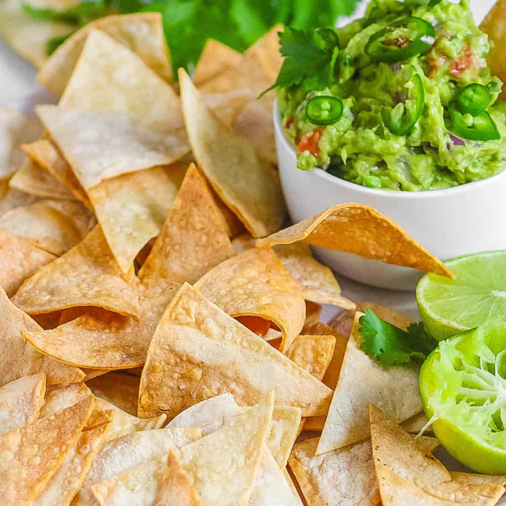 air fryer tortilla chips served with guacamole on a white plate