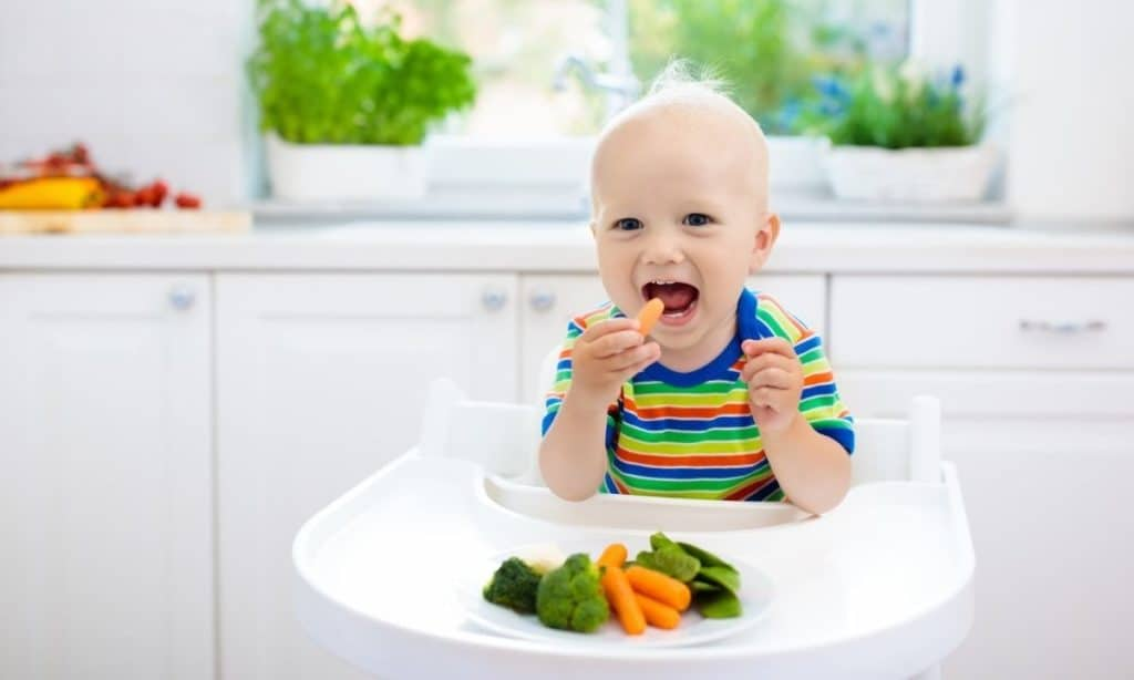 Baby in high chair with carrots, broccoli, and snap peas.