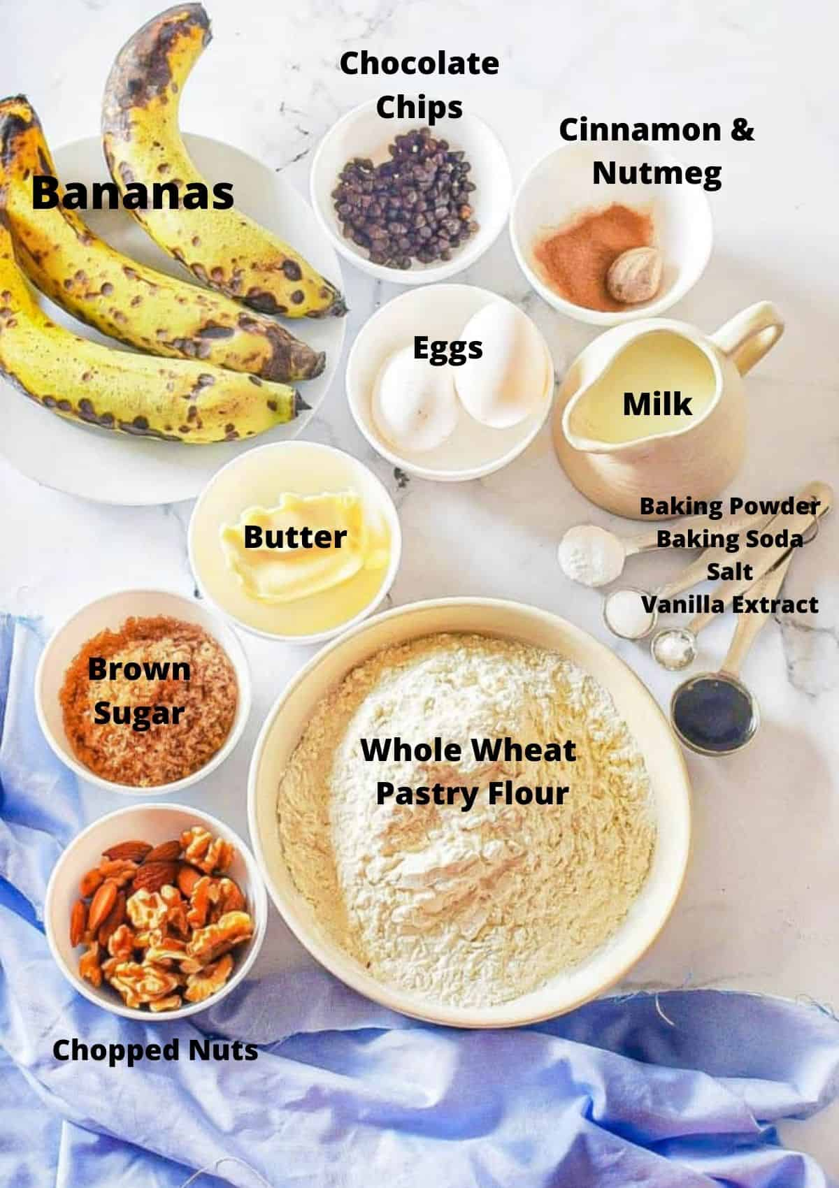 Ingredients for chocolate chip banana muffins on counter top: bananas, eggs, butter, spices, milk, baking powder, baking soda, salt, vanilla, whole wheat pastry flour, chopped nuts, and brown sugar.