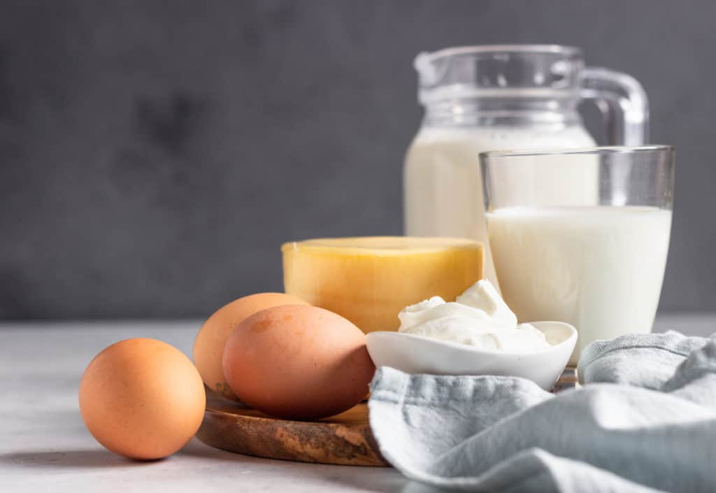 foods that start with d - Different types of fresh dairy products and eggs on wooden plate. Natural farm products.
