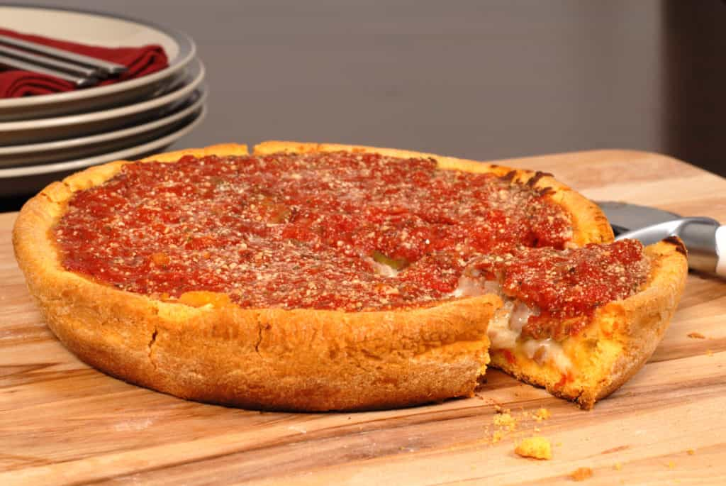 A Chicago style deep dish pizza with a piece cut out