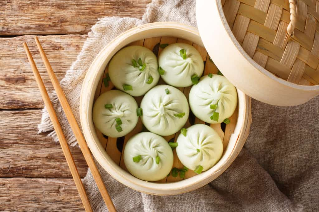 Traditional chinese baozi steam buns in a bamboo steamer basket close-up on the table. Horizontal top view from above