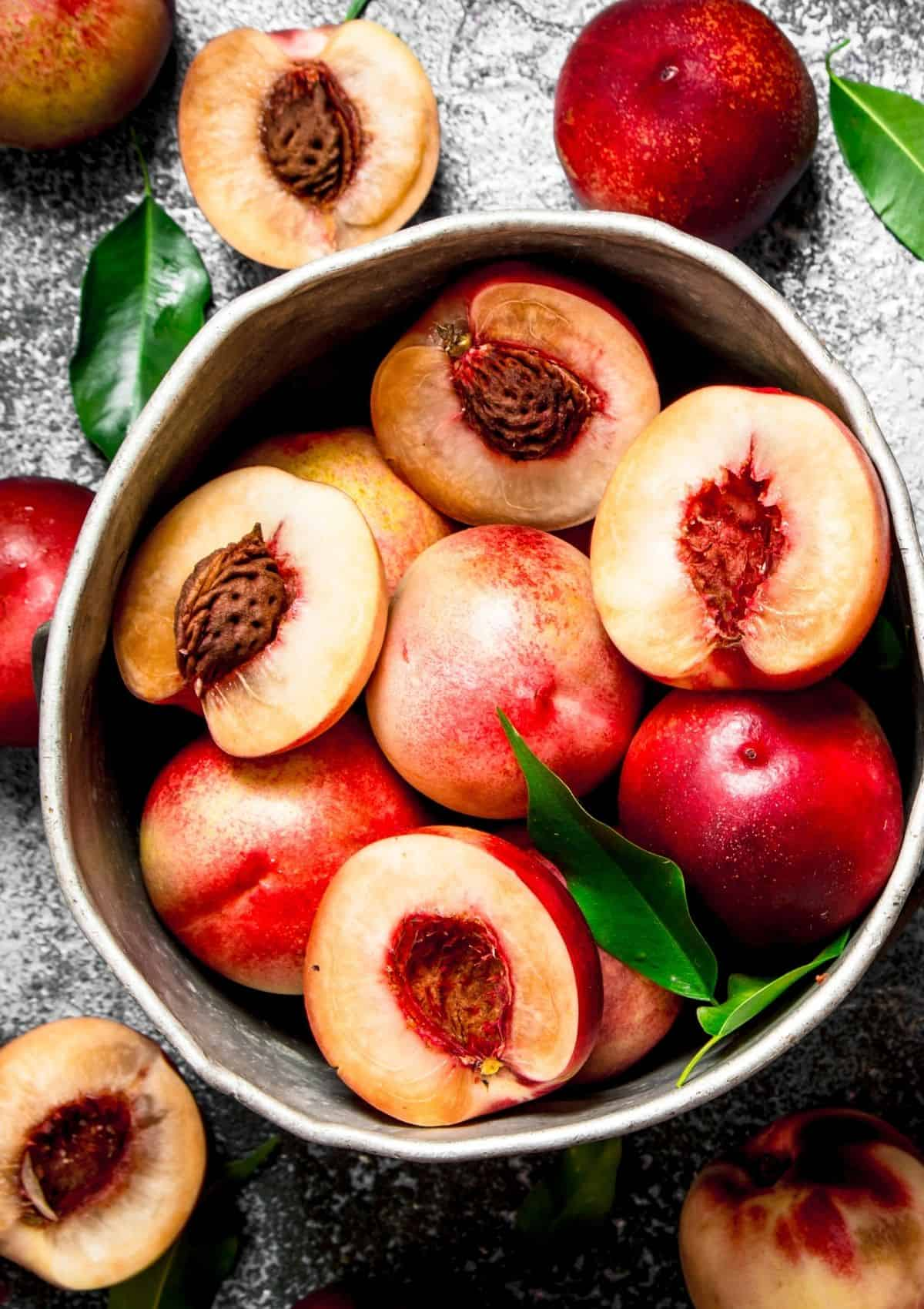 Nectarines cut in half in bowl (foods that start with n)
