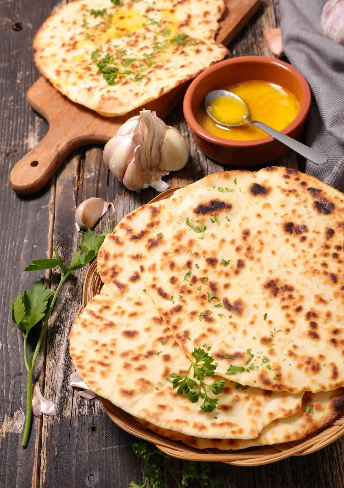 Naan bread stacked on flat basket.