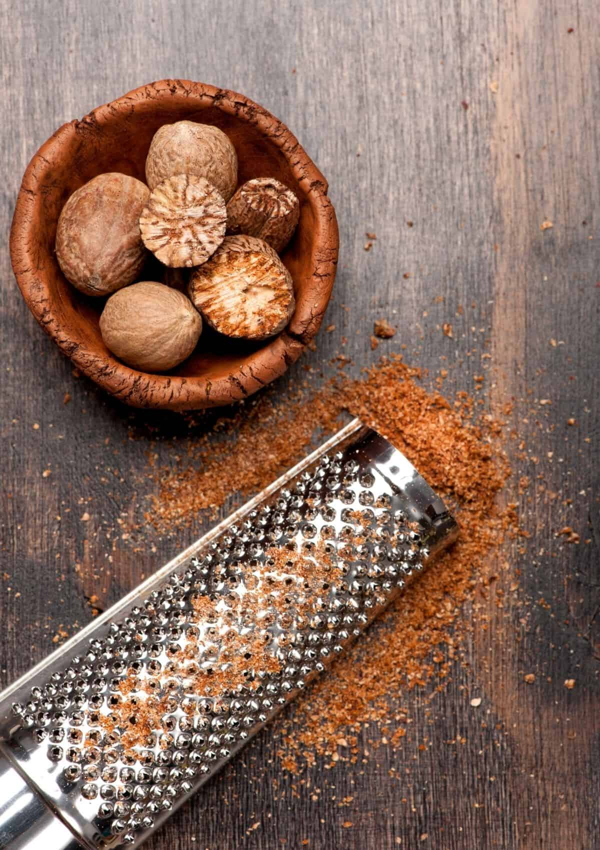 Nutmeg  in small wood bowl, beside ground nutmeg. - foods that start with n