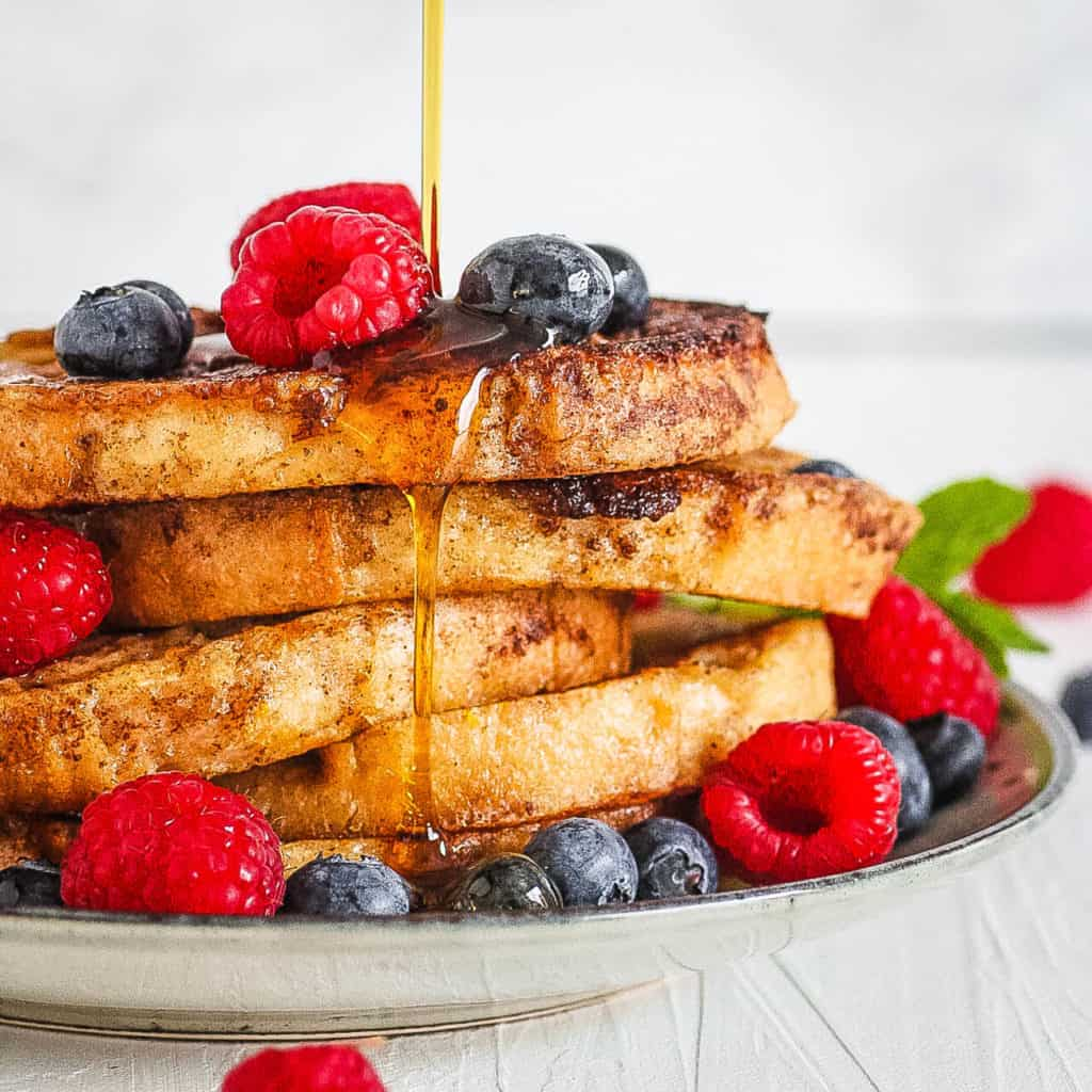 easy low calorie healthy french toast with berries and syrup served on a white plate