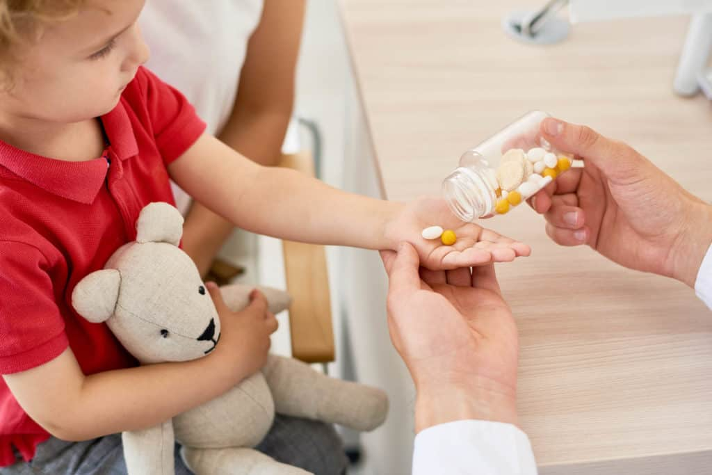 best kids vitamin for brain development - Closeup of unrecognizable doctor giving vitamins to curly little boy during appointment