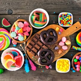Colorful sweet low calorie candy buffet table scene. Above view over a rustic wood background.
