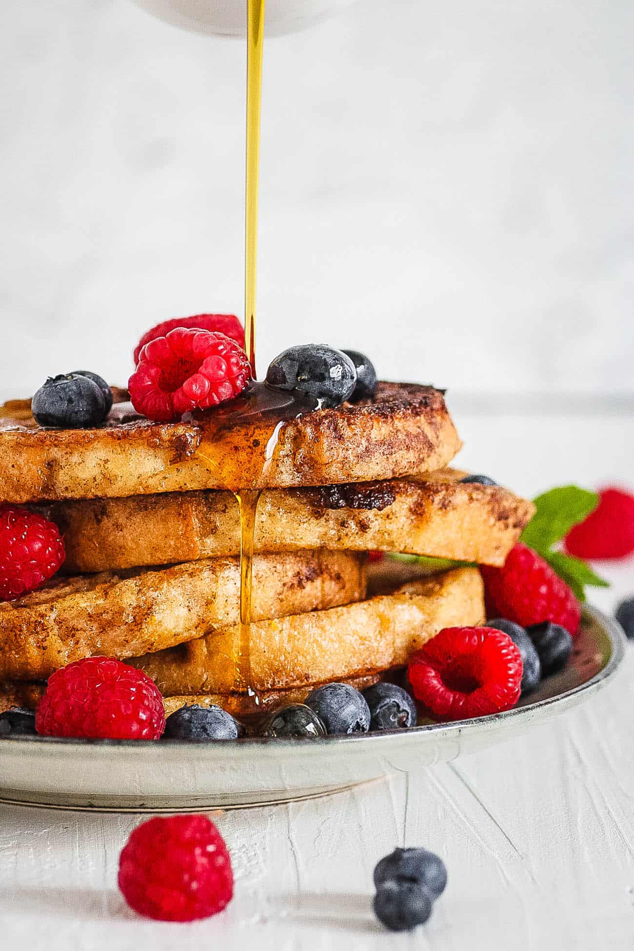 quick healthy french toast with berries and syrup served on a white plate