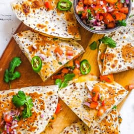 vegan quesadillas made with butternut squash and kale topped with pico de gallo on a cutting board