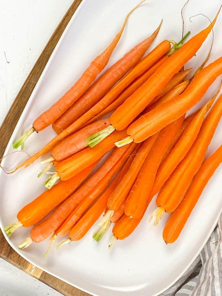 freshly peeled carrots on a white plate