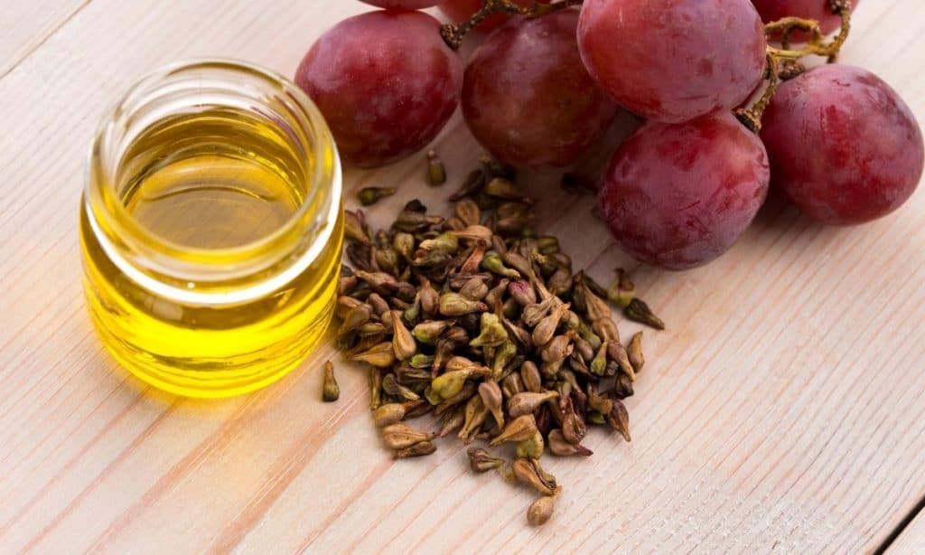 Grapeseed oil in small jar beside pile of grapeseeds and red grapes. - best oil to season cast iron