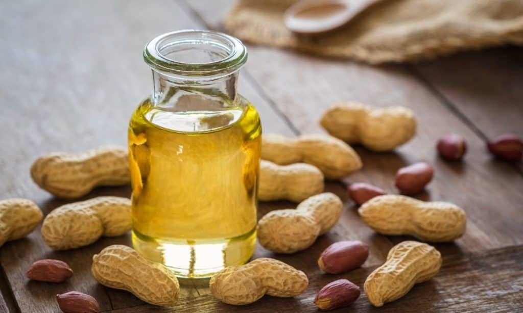 Peanut oil in small jar, surrounded by peanuts and peanut shells.