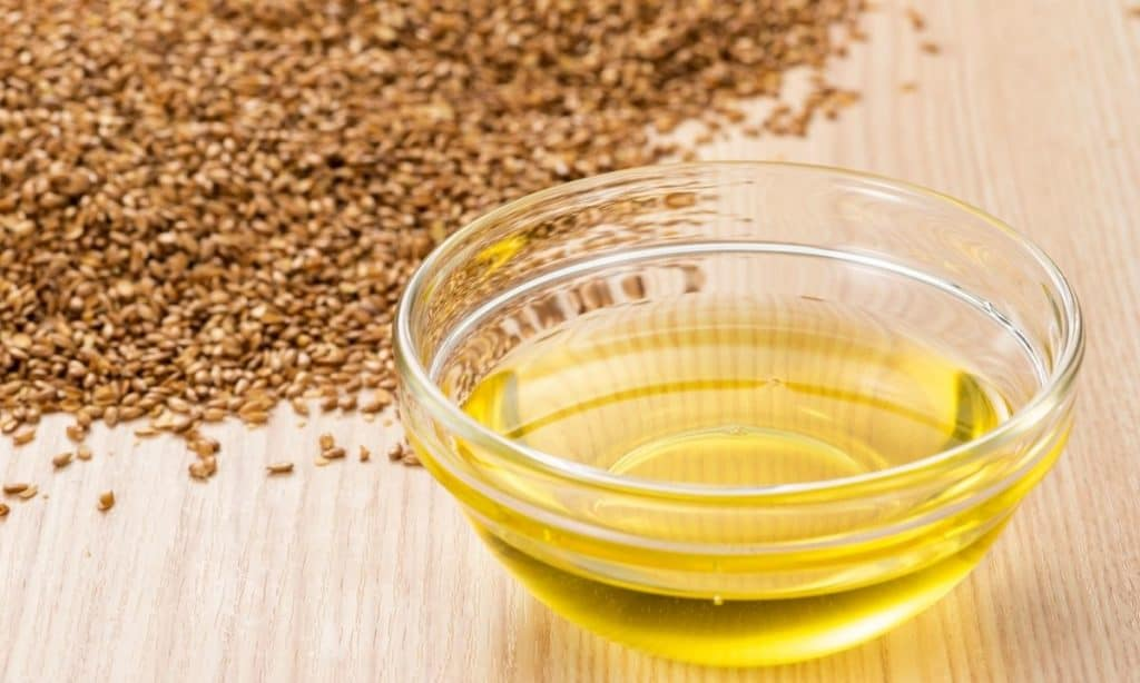 Flaxseed oil in small glass bowl beside flaxseeds on wood countertop.