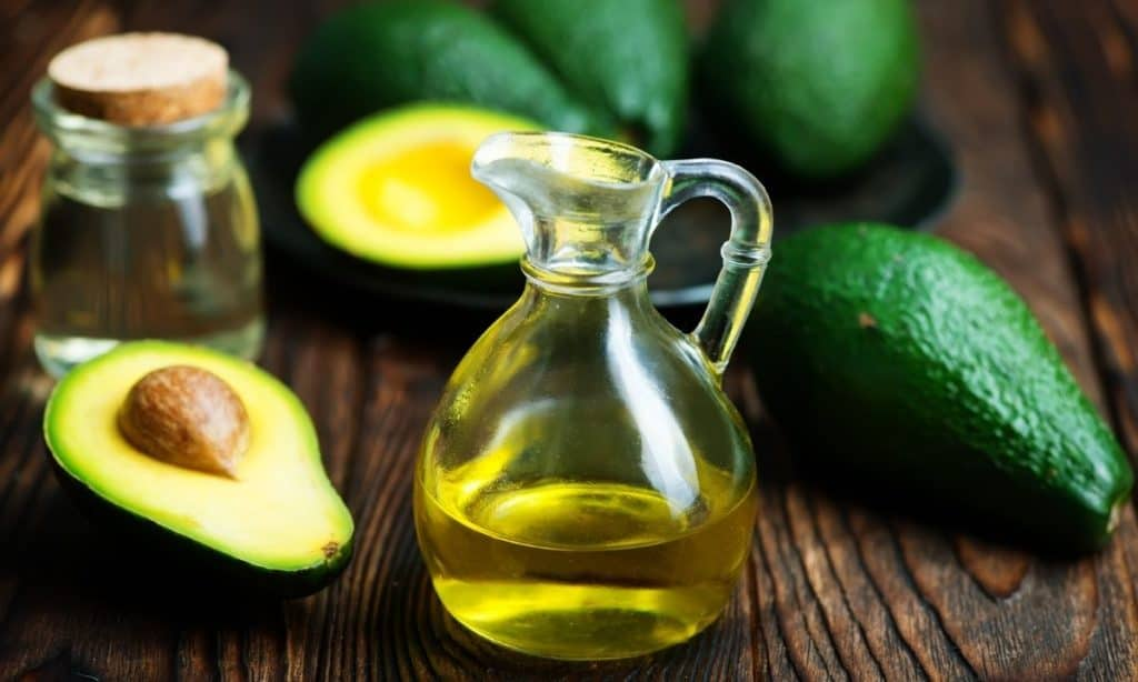 Avocado oil in small pouring jar, surrounded by fresh avocadoes.
