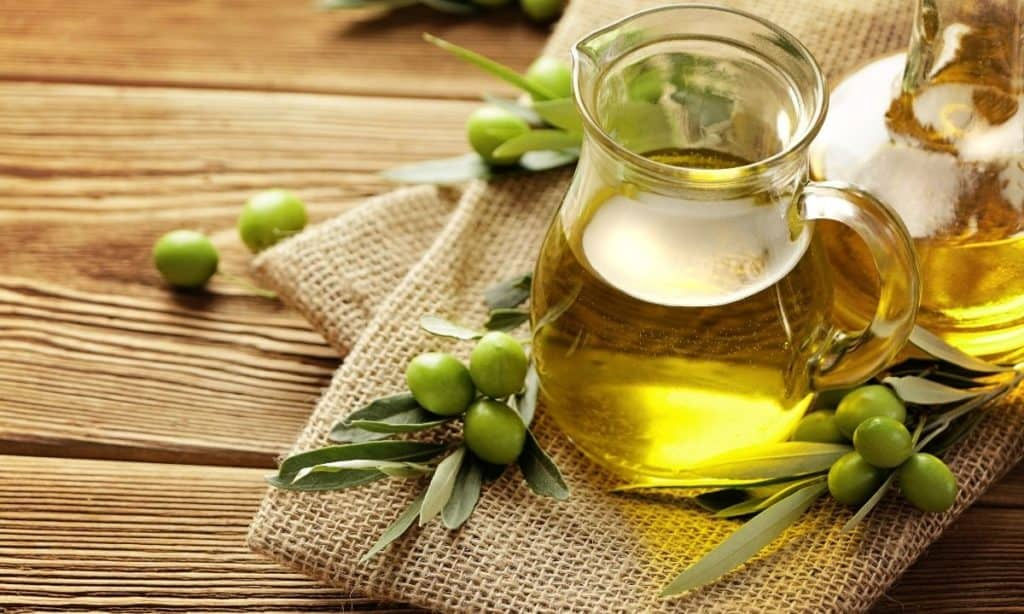 Olive oil in small pitcher surrounded by green olives.