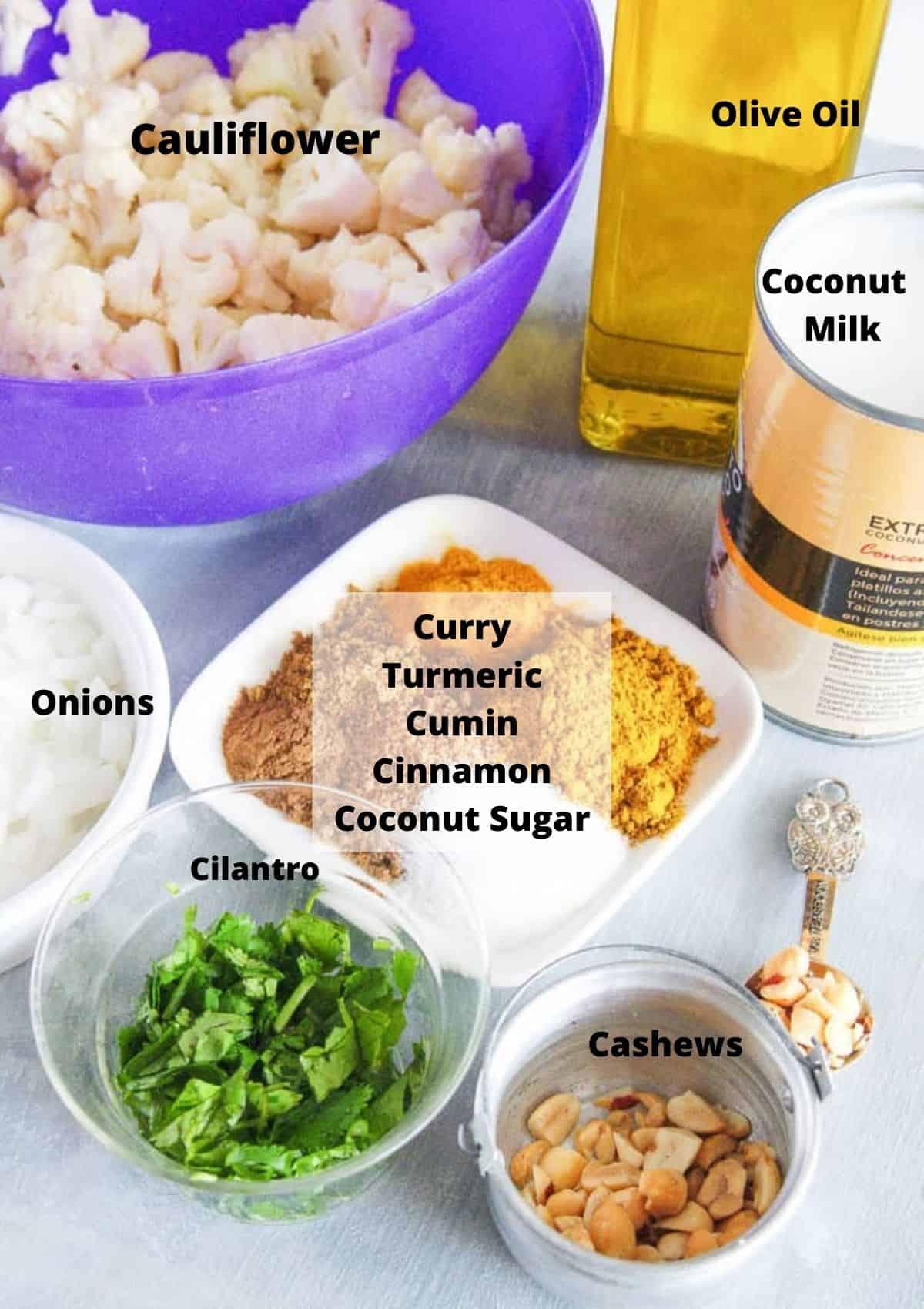 Cauliflower soup ingredients: Chopped cauliflower florets, olive oil, coconut milk, spices, cashews, cilantro, onions.