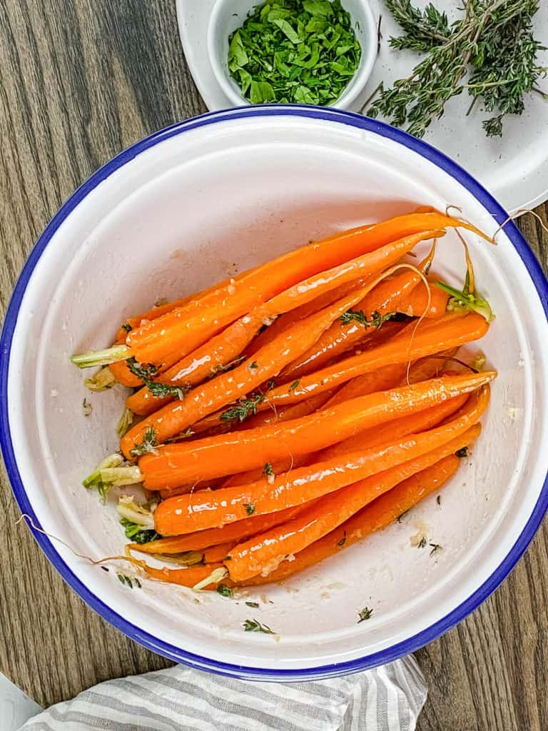 carrots mixed with herbs and olive oil in a white bowl