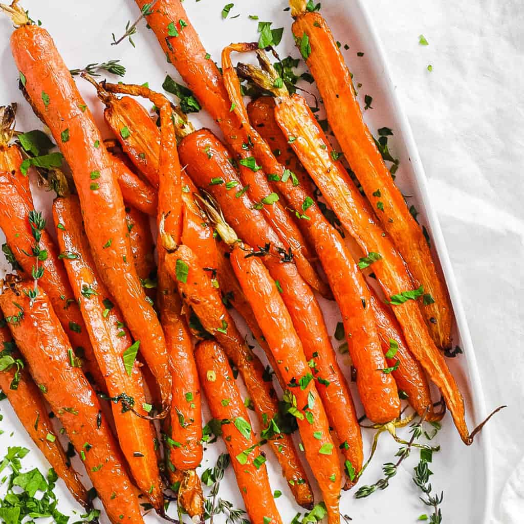 easy delicious air fried carrots served with fresh herbs on a white plate
