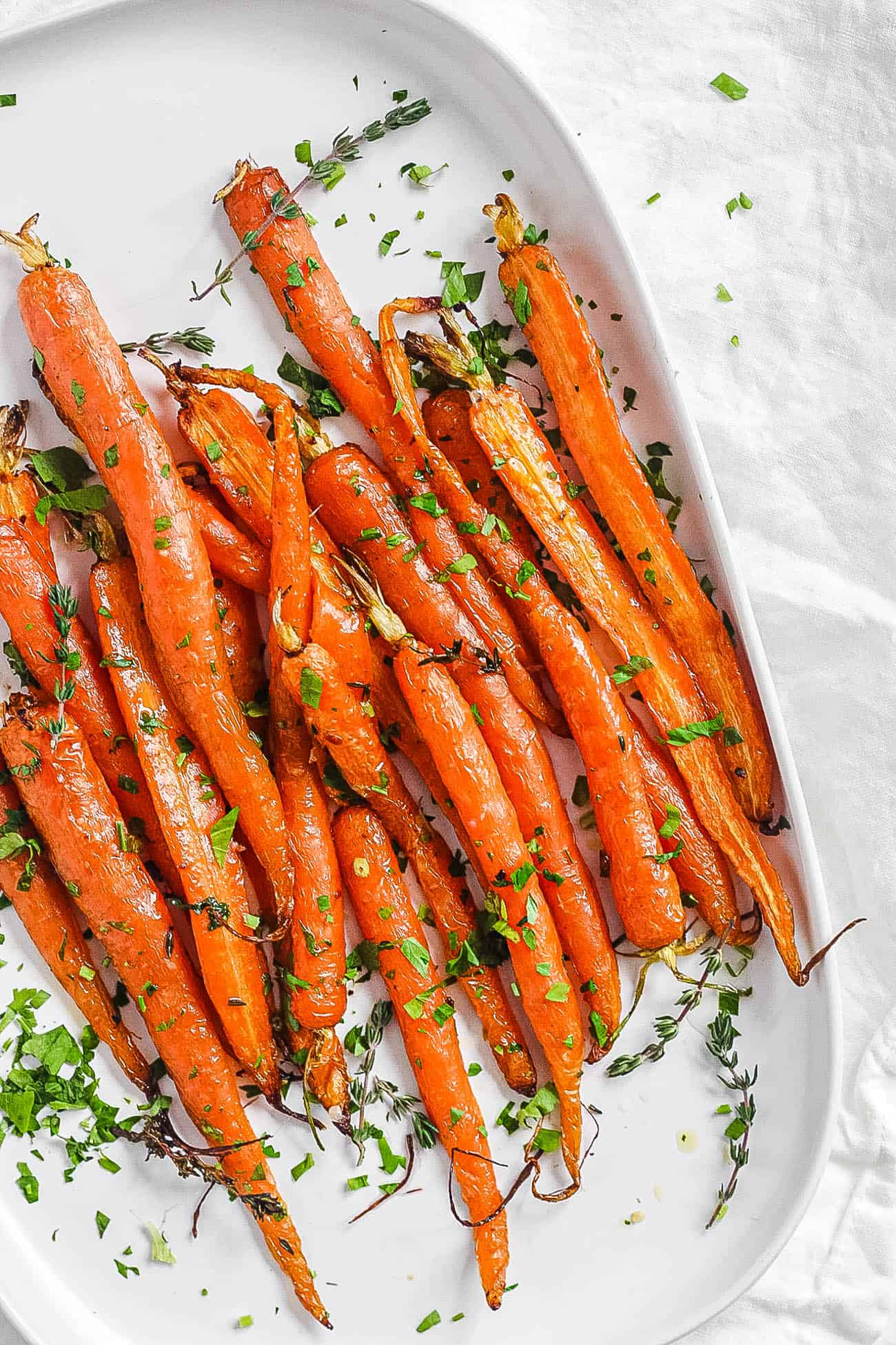 easy delicious air fryer carrots served with fresh herbs on a white plate