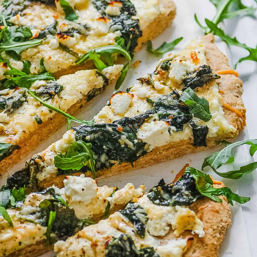 vegetarian florentine pizza - white pizza with spinach and parmesan cheese, sliced on a white platter