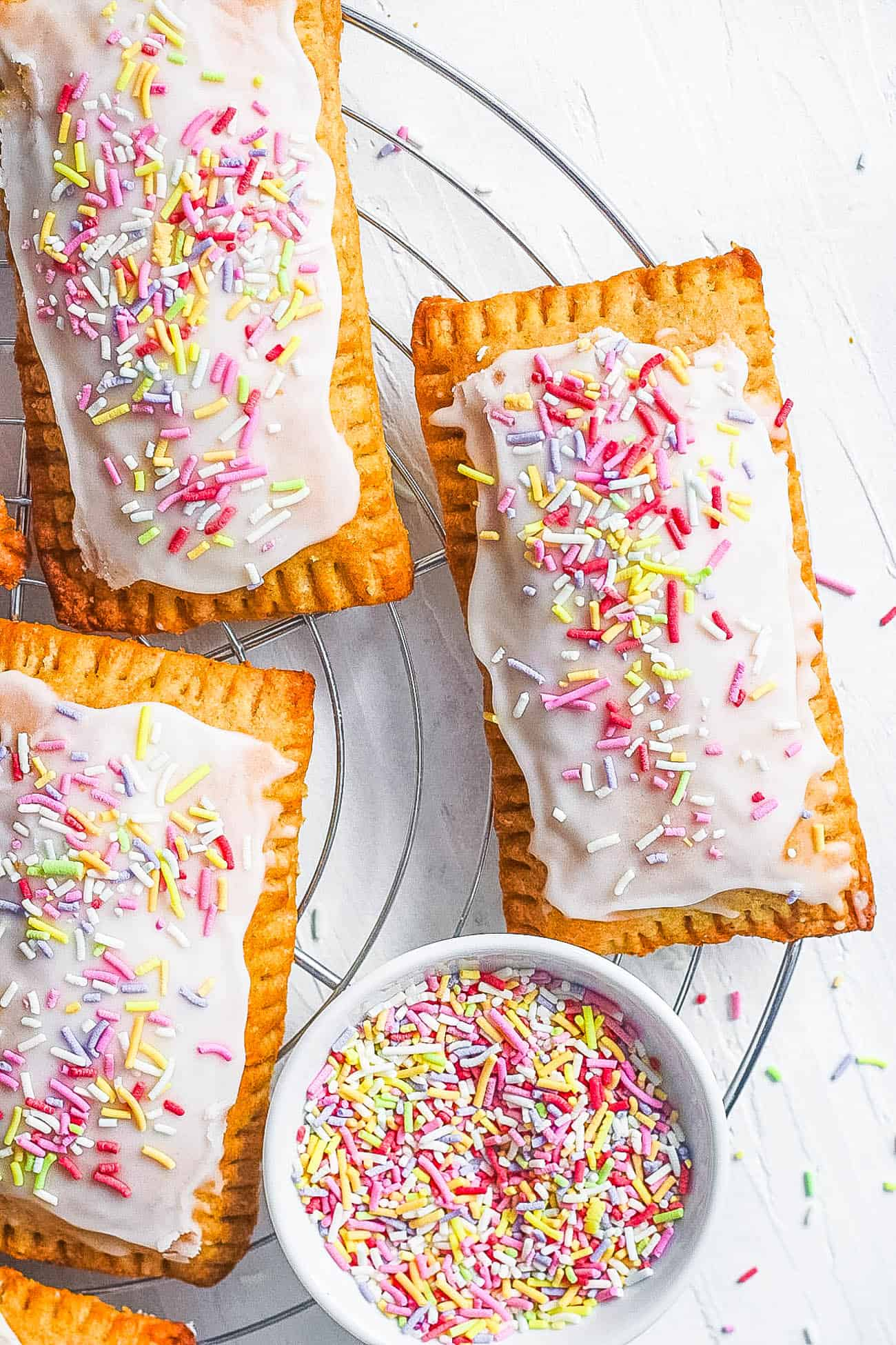 healthy homemade vegan pop tarts with strawberry filling with rainbow sprinkles and coconut yogurt icing