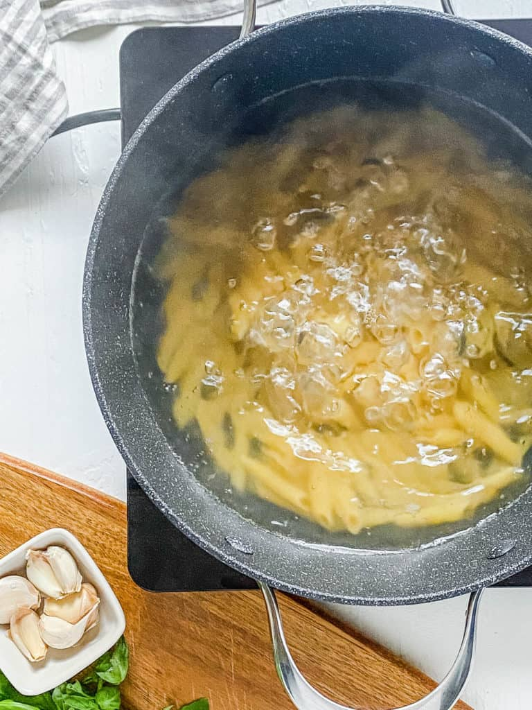 whole wheat penne pasta cooking in a stock pot