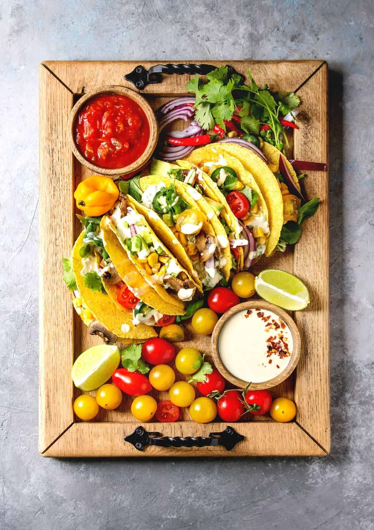 Vegetarian tacos with lots of taco toppings on wood cutting board, surrounded by taco toppings such as salsa, cilantro, onion, peppers, tomatoes, and a creamy dressing.