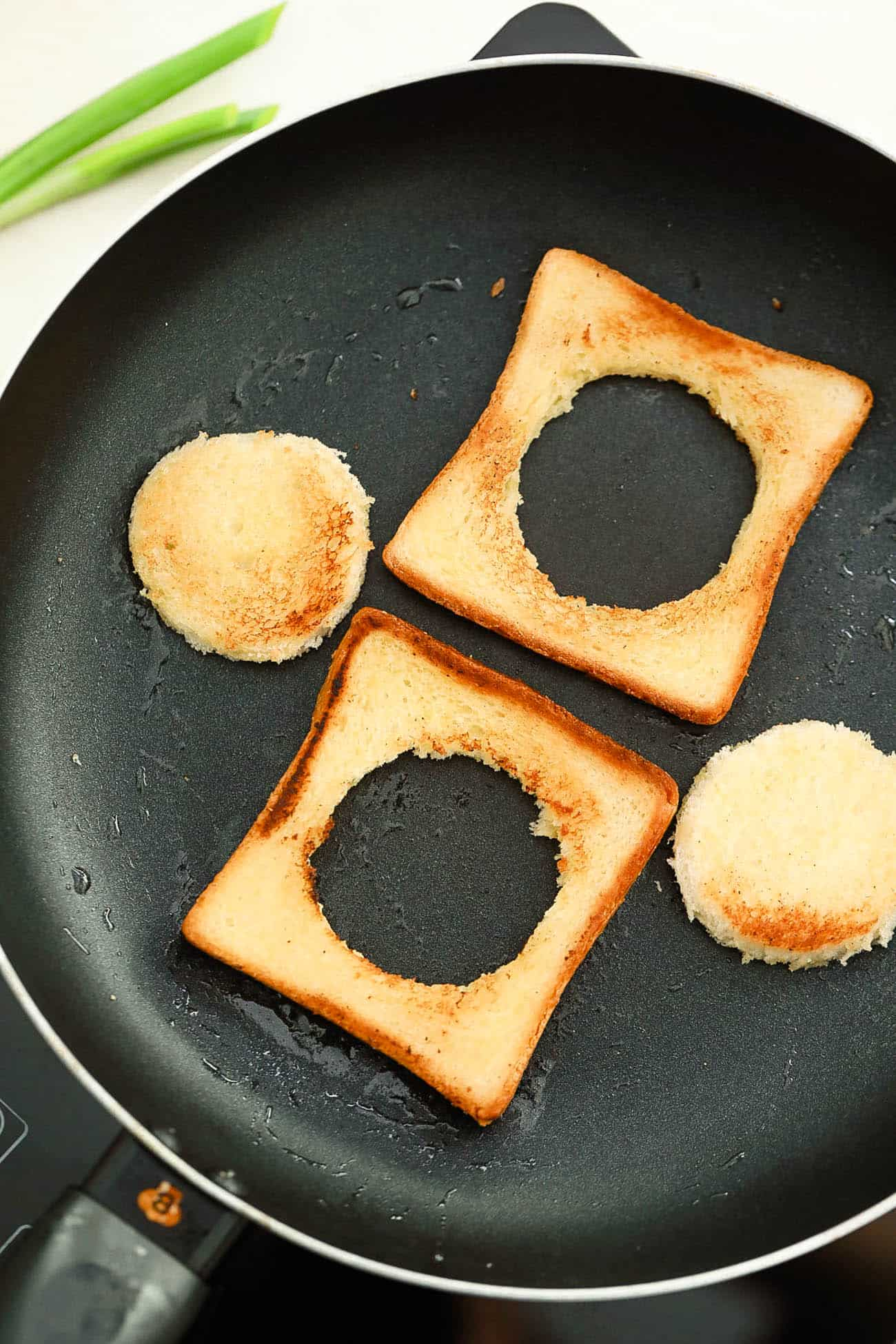 bread toasting in a skillet with a hole cut out of the center