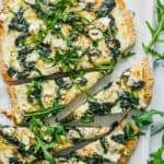 vegetarian florentine pizza - white pizza with spinach and parmesan cheese on a white platter