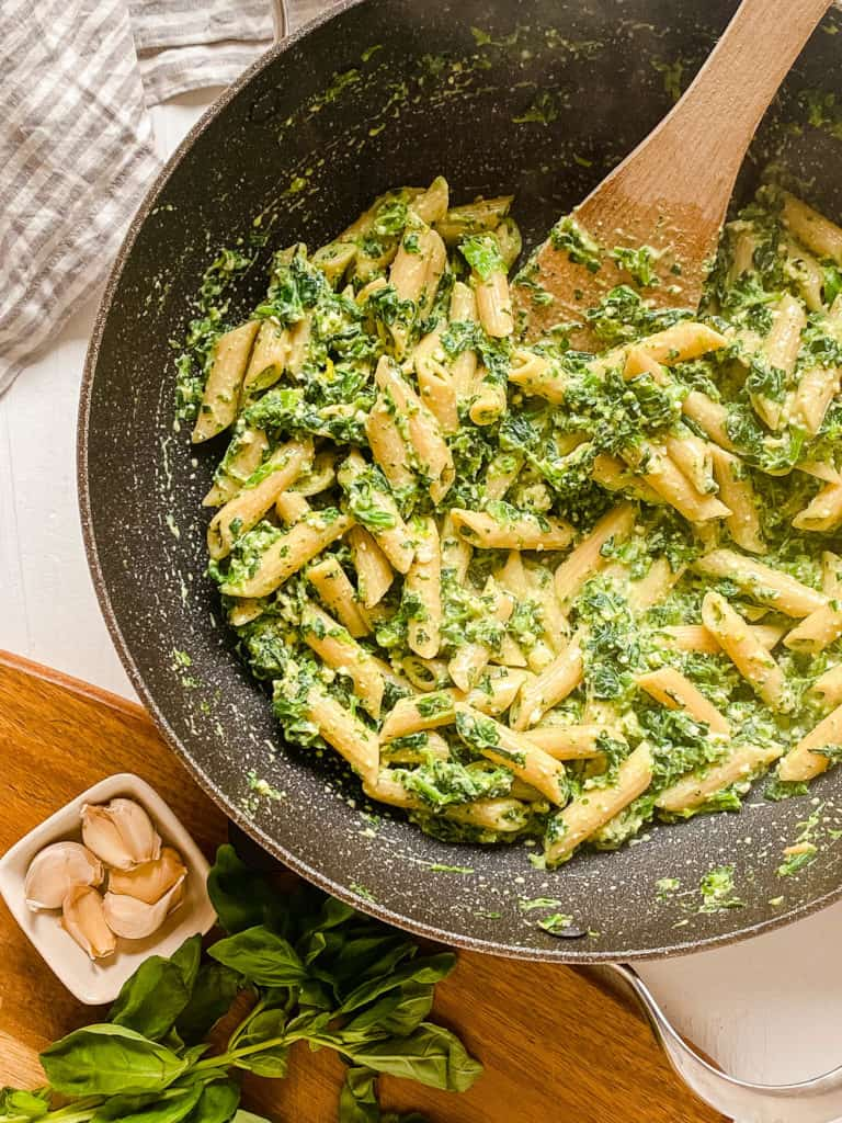 vegetarian pesto pasta recipe with spinach, basil and pine nuts in a skillet