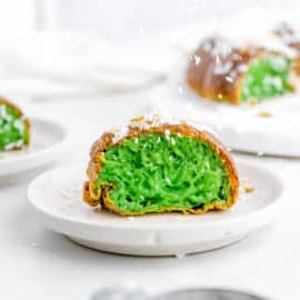 banh bo nuong - Vietnamese honeycomb Cake cut to show green pandan inside, served on a white plate