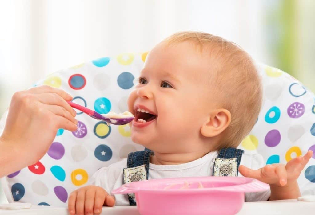 Happy baby in high chair eating oat cereal.