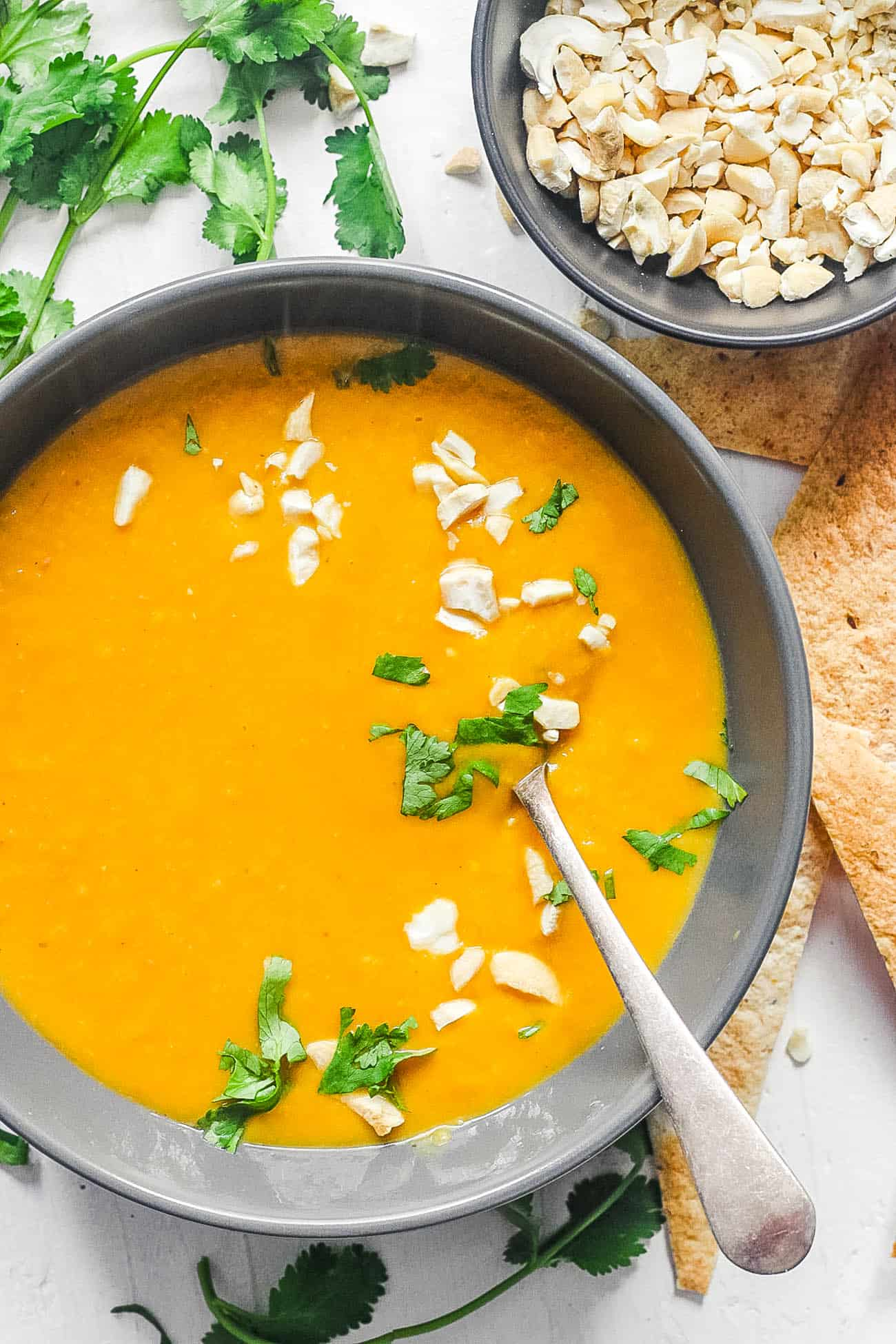 creamy butternut squash soup with coconut milk, cilantro and crushed nuts served in a black bowl